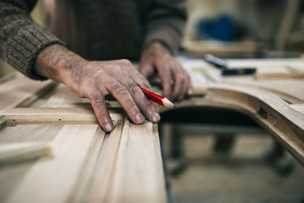 Close up shot of old master carpenter working in his woodwork or workshop